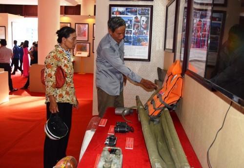 Bà Bùi Thị Thái đang xem lại các tư liệu quý trong triển lãm.