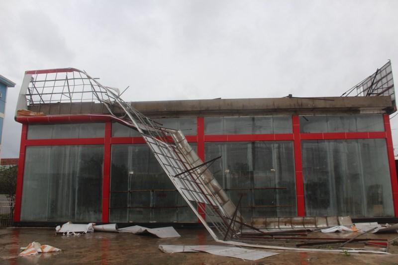 Nhiều ngôi nhà bị tốc mái, biển hiệu bị gãy đổ, nằm rạp.Ảnh: Nguyễn Do