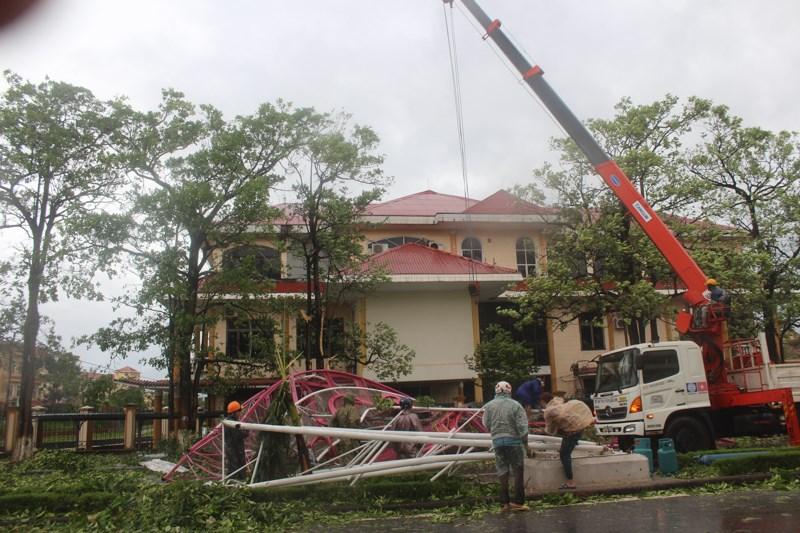 Lực lượng chức năng đang khẩn trương tháo dỡ một cổng chào trang trí bị gãy đổ trong bão.Ảnh: Nguyễn Do