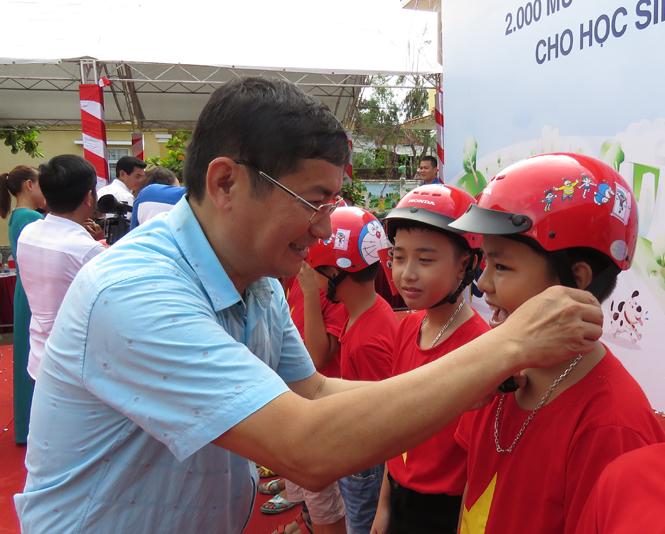 Đồng chí Trần Tiến Dũng, Tỉnh ủy viên, Phó Chủ tịch UBND tỉnh đội mũ bảo hiểm cho các em học sinh Trường tiểu học Hải Thành.