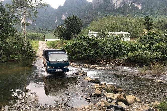 Huy lái xe vượt suối để giao sản phẩm cho khách hàng.