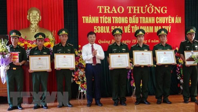 Chủ tịch Ủy ban Nhân dân tỉnh Quảng Bình trao thưởng cho cá nhân, tập thể trong chuyên án. (Ảnh: Đức Thọ/TTXVN)