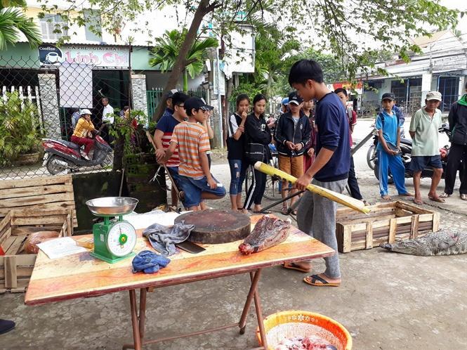 Người đàn ông đang xẻ thịt cá sấu bán ngay bên đường