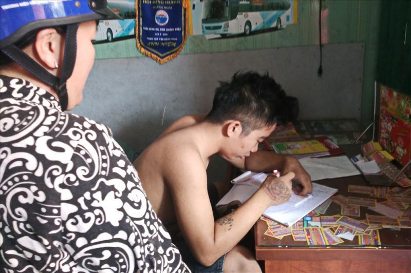 Nhân viên hãng xe dù trên đường Hồng Lạc (Q.Tân Bình, TPHCM) đang ghi vé xe tết TPHCM đi Quảng Ngãi bán cho khách. Ảnh: MINH QUÂN 7-3.jpg