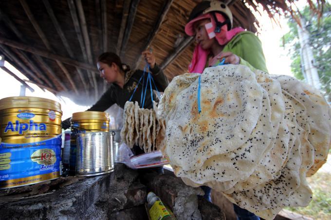 Người dân trong xã mang bánh tráng đến xếp hàng ở lò nấu đường của nhà ông Trần Đình Hai, chờ nhúng vào chảo.