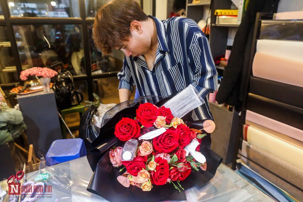 """Chị Phương cho biết, trong ngày 13 và ngày 14/2, cửa hàng đã bán được hơn chục bó hoa như nói trên. """"Mình cho thêm vào hoặc nhiều khách tự mang thêm khẩu trang và nước xịt khuẩn tới nhờ gắn thêm""""."""