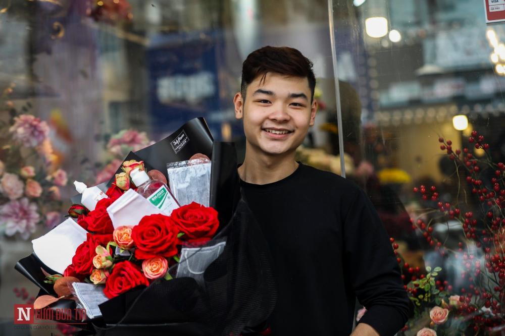"""Cầm trên tay bó hoa vừa đặt hàng, anh Lại Thái Phong (Hà Nội) tỏ ra khá thích thú khi đặt làm một bó hoa hồng khô, và nhờ đính thêm một số đồ phòng dịch để mang đi tặng bạn gái. Anh cho biết: """"Năm ngoái em tặng Socola, năm nay muốn thay đổi một chút. Em muốn kèm thêm một số thứ cho vui, tạo sự bất ngờ cho bạn gái""""."""
