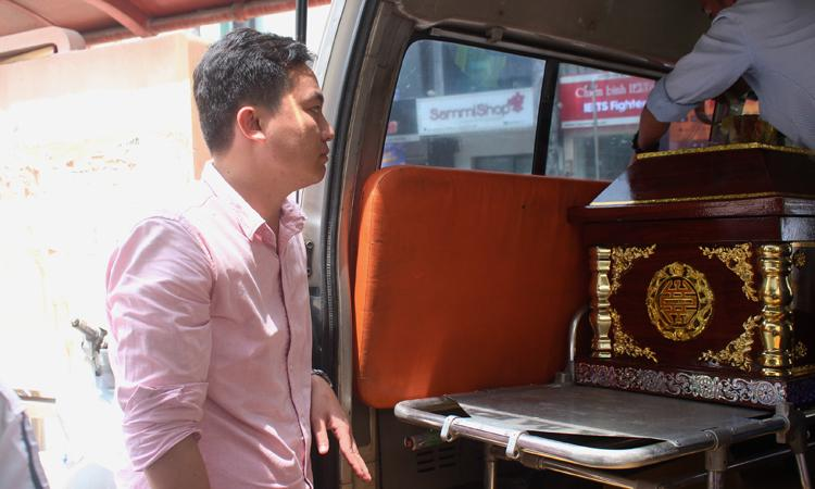Nghị (áo hồng) nán lại với gia đình, chờ đến lúc đưa quan tài bé lên xe. Ảnh: Diệp Phan