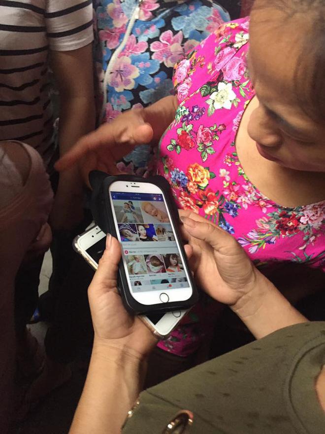 Người dân mở điện thoại xem lại ảnh trên facebook của nghi phạm.