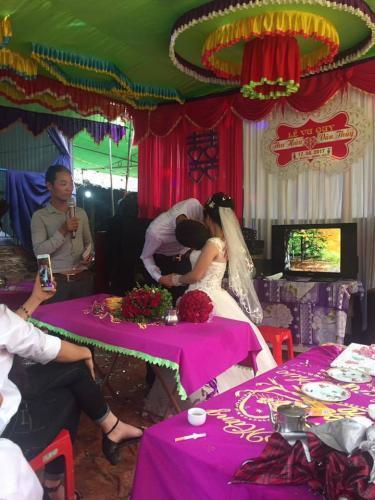 Chú rể... vất vả hôn cô dâu trong ngày cưới. Ảnh: Facebook Hoàng Sơn