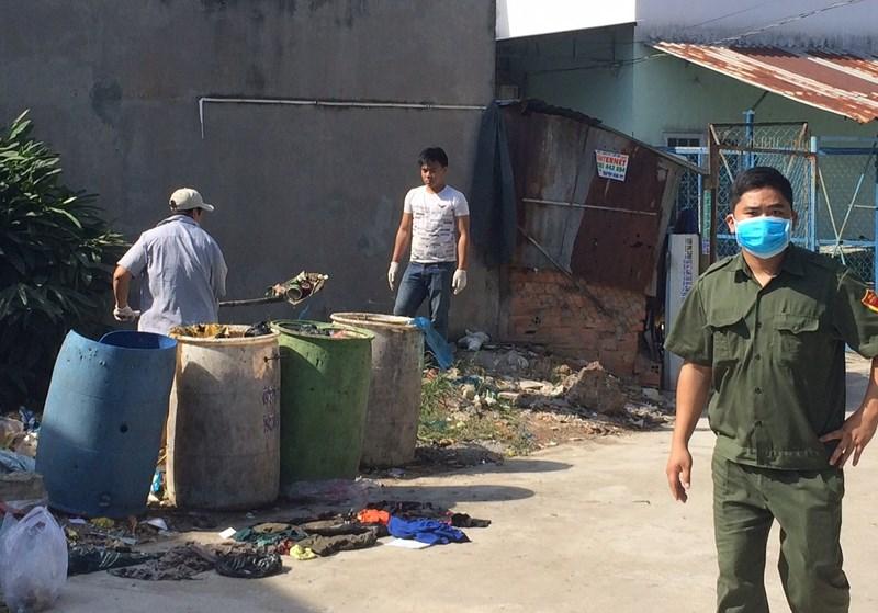 Lực lượng chức năng tìm kiếm khu vực bỏ rác của nhà trọ nơi vợ chồng nạn nhân sinh sống. Ảnh: Vũ Hội.