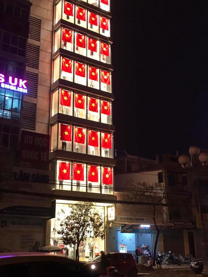 Một cửa hàng thời trang trang trí cực bắt mắt với mỗi ô kính được treo 1 lá cờ đỏ sao vàng.