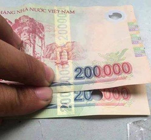 Tờ tiền giả (bị đục lỗ) có vệt phản quang bị hụt so với tờ tiền thật.