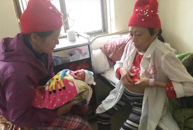 Chị Quyên (bìa phải) cùng bà nội sung sướng chăm sóc con trai. Ảnh: Duy Chiến.