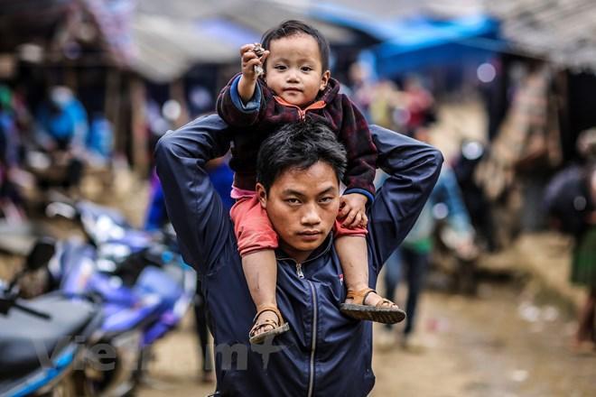 Những đứa trẻ dân tộc được bố mẹ đưa xuống chợ chơi. (Ảnh: Phạm Hương/Vietnam+)