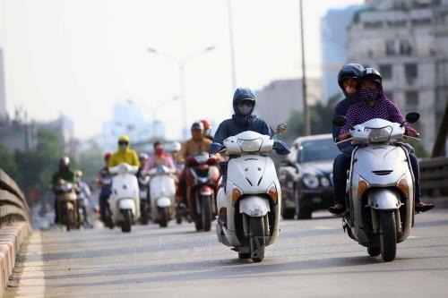 Mặc áo chống nắng là lựa chọn tốt nhất mỗi khi phải tham gia giao thông trong thời tiết nắng nóng. Ảnh: Quang Quyết/TTXVN