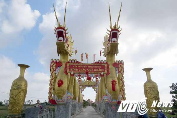 """Đôi tượng rồng chầu rực rỡ màu vàng cao 18m,  dài 63m, hai chân trước đôi rồng nâng tấm biển: """"Bản Phủ Phúc Sinh Trường kính chào quý khách"""" với giá trị xây dựng  trên 3 tỷ đồng."""