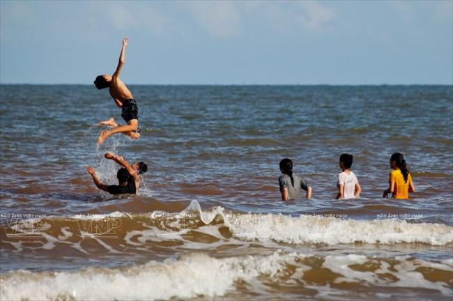 Du khách thích thú với sóng biển.