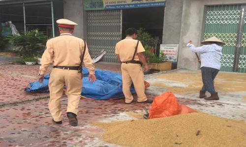 Cảnh sát giao thông giúp dân dọn lúa