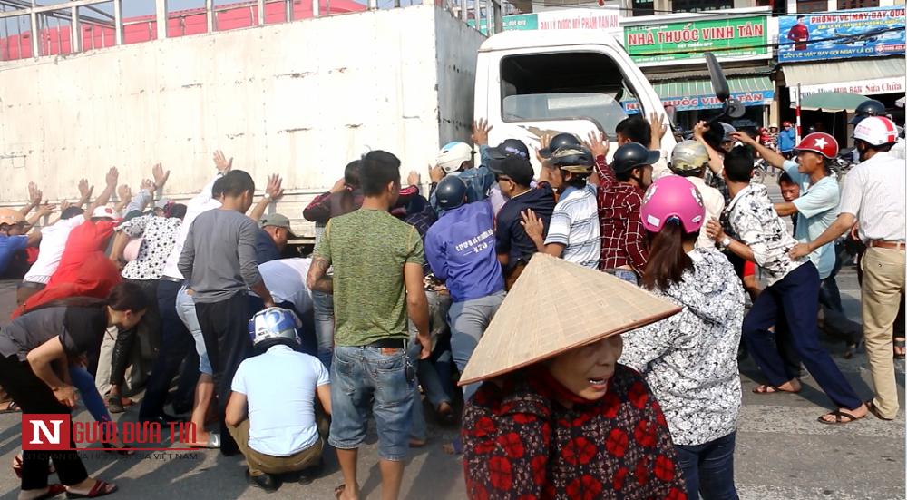 Hàng chục người dân nhấc bổng chiếc xe tải, giải cứu các nạn nhân.