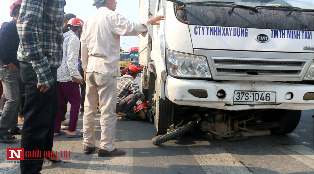 2 nạn nhân và chiếc xe máy bị mắc kẹt dưới gầm xe tải.