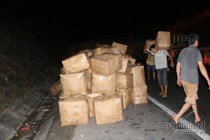 Hàng chục thùng trái cây trên xe tải gặp nạn được thu gom trong nỗ lực thông tuyến quốc lộ. Ảnh: Quang Thành