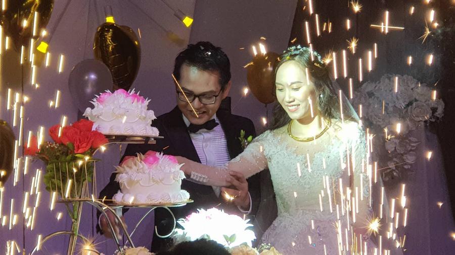 Cô dâu chú rể cắt bánh cưới trong niềm hạnh phúc.