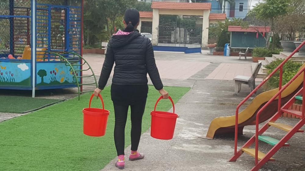 Xách xô đi xin nước nấu cơm cho học sinh là việc của các cô giáo Trường Mầm non Thái Thịnh những ngày qua.