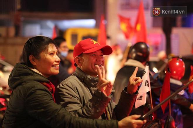 2 cô chú mỉm cười tươi rói trong không khí ăn mừng chiến thắng của ĐT Việt Nam. Ảnh: Việt Anh.