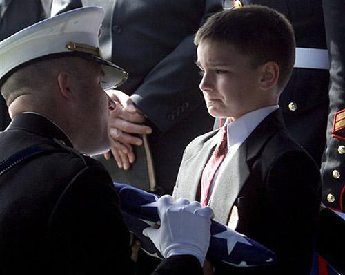 Giấu giọt nước mắt vào trong và cắn chặt môi để khỏi bật khóc, cậu bé 8 tuổi Christian Golczynski nhìn thẳng vào mắt người lính hải quân đang trao lại cho mình lá cờ Mỹ gấp gọn gàng. Lá cờ này đã được phủ lên quan tài của cha cậu khi chuyển về quê nhà. Hình ảnh cậu bé trong bức ảnh