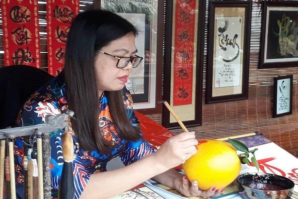 Viết thư pháp trên trái bưởi để trưng bày trong dịp tết