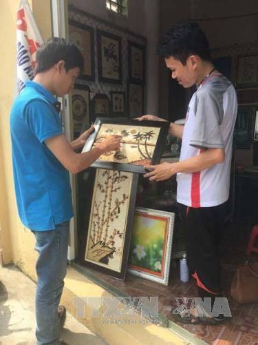 Cao Văn Tuân tư vấn cho khách hàng mua tranh gạo.