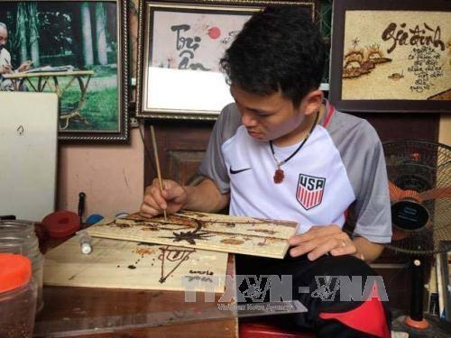 Cao Văn Tuân đang hoàn thiện tác phẩm tranh gạo.