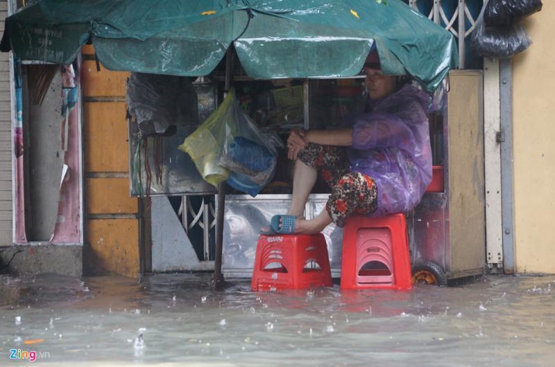 Mưa ngập cả vỉa hè khiến người phụ nữ bán nước, đồ ăn vặt ở đường Tô Vĩnh Diện chỉ biết ngồi ngắm phố và trông coi tài sản. Theo dự báo, đến hết ngày 16/9, lượng mưa trên địa bàn tỉnh Thanh Hóa vẫn chưa thuyên giảm.