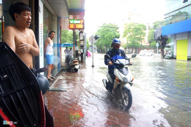 Tại đường Tô Vĩnh Diện, nước gần tràn vào nhà dân ở ven đường. Nhiều xe máy phải lao lên cả vỉa hè vì không thể đi dưới lòng đường.