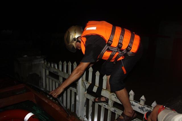 Lực lượng cứu hộ trèo qua cổng vào nhà cứu dân