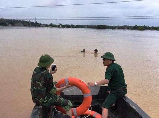Đại úy Nguyễn Văn Hùng (bìa phải) đang cho thuyền tiếp cận 2 bố con ông Sức đang chơi vơi giữa dòng nước lũ