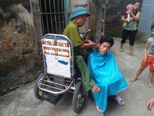 Dù ngồi trên xe lăn, đôi tay co quắp nhưng tay nghề của ông Tý không kém các thợ cắt tóc ở tiệm là mấy.