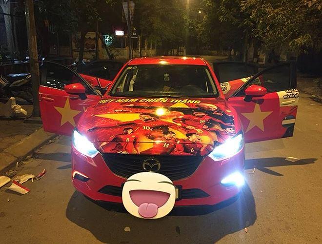 Chiếc Mazda này được chủ nhân phủ kín với cờ Tổ quốc và hình ảnh thầy trò HLV Park Hang-seo trên nắp ca-pô