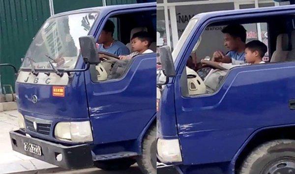 Bé trai lái xe trong sự thản nhiên người của đàn ông ngồi bên cạnh.