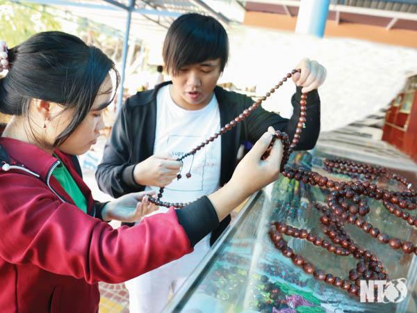 Du khách chọn mua sản phẩm thủ công mỹ nghệ được làm bằng hạt cây rừng tại Điểm du lịch suối Lồ Ồ.