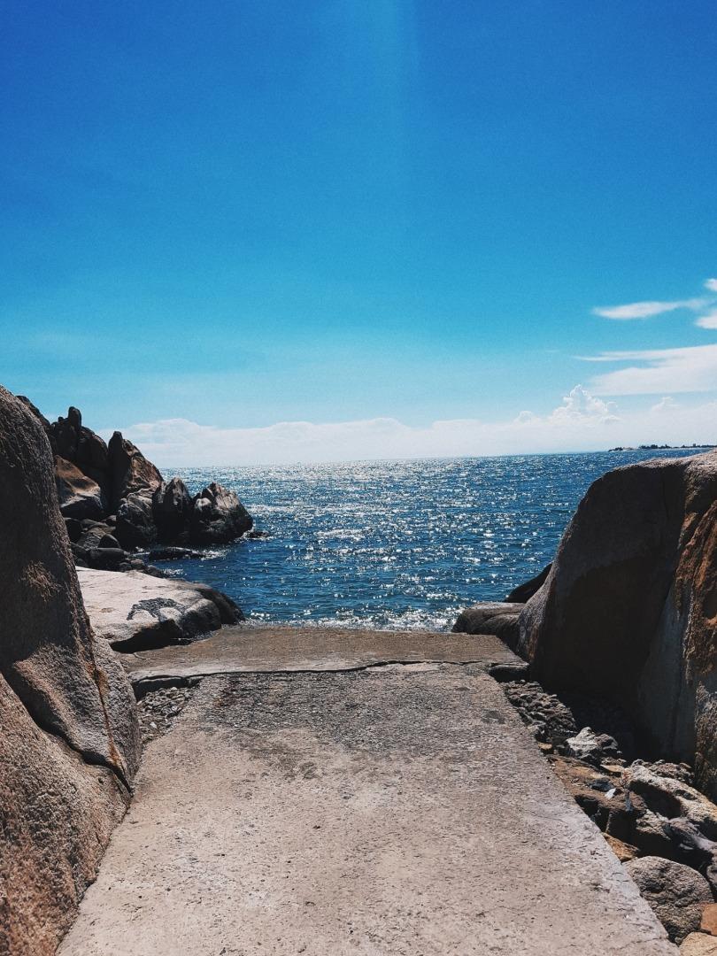 Những tảng đá lớn kết hợp với nước biển trong xanh, lấp lánh trong nắng vàng