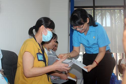Bà Trần Thị Diệu Thúy, Chủ tịch LĐLĐ TP HCM, tặng quà cho công nhân Công ty CP Giày da Huê Phong (quận Gò Vấp, TP HCM)