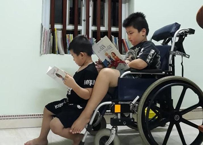 Bé Longtruyền đam mê đọc sách cho cậu em ruột