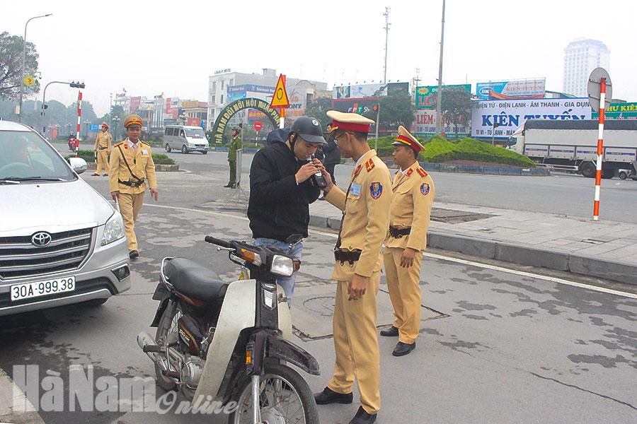 Lực lượng Cảnh sát giao thông Công an thành phố Phủ Lý kiểm tra nồng độ cồn đối với tài xế xe mô tô. Ảnh: Mai Hương