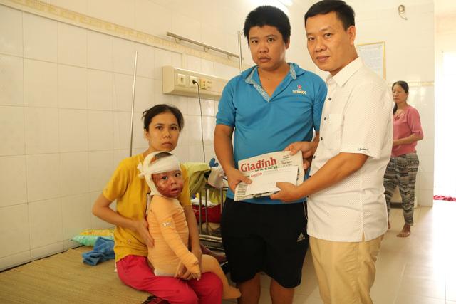 Ông Nguyễn Ngọc Đức - Phó Tổng biên tập Báo Gia đình và Xã hội trao tiền cho gia đình anh Thường. Ảnh PT