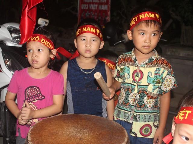 Nhiều trẻ nhỏ mang theo cờ, trống, đeo băng rôn đến cổ vũ