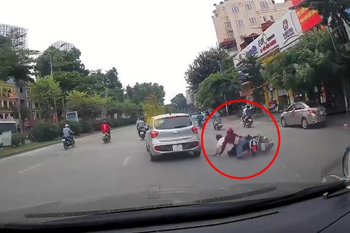 Hai người đi xe máy bị hất tung xuống đường (Ảnh từ clip)