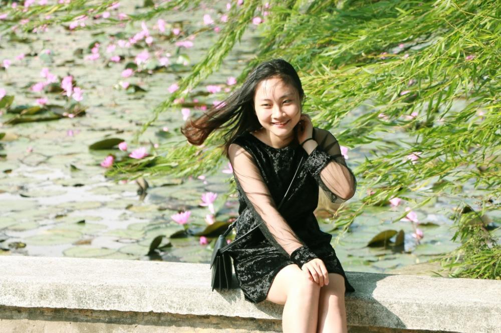 Nữ sinh tạo dáng bên hồ hoa s úng, dưới nắng vàng cuối thu cùng cành liễu rủ