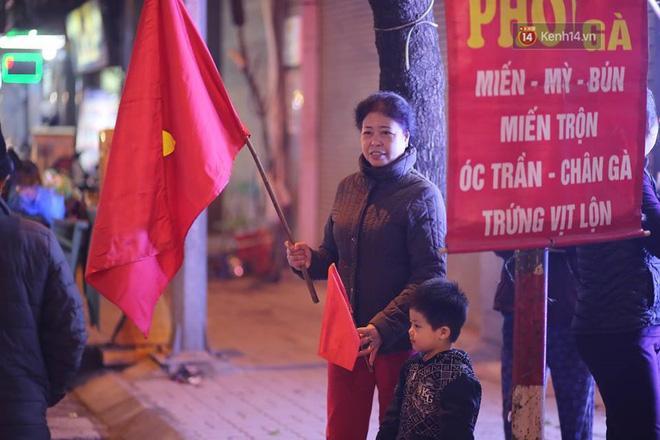 Hai bà cháu cầm cờ ra đường ngay sau chiến thắng của ĐT Việt Nam. Ảnh: Việt Anh.